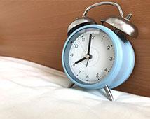 ベッドの上の目覚まし時計